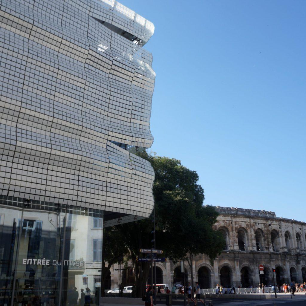 vue de la façade du musée de la romanité avec les arènes de Nîmes en arrière plan