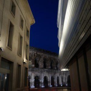 vue en perspective depuis une rue jouxtant le musée - les arènes de Nîmes en arrière plan
