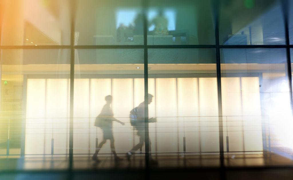 silhouettes de visiteurs déambulant dans une allée du musée
