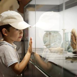 jeune garçon devant une vitrine où sont exposés des pièces antiques