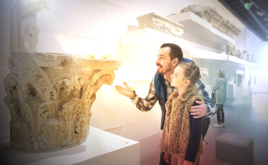 visiteurs contemplant des éléments décoratifs de l'architecture de la période romaine