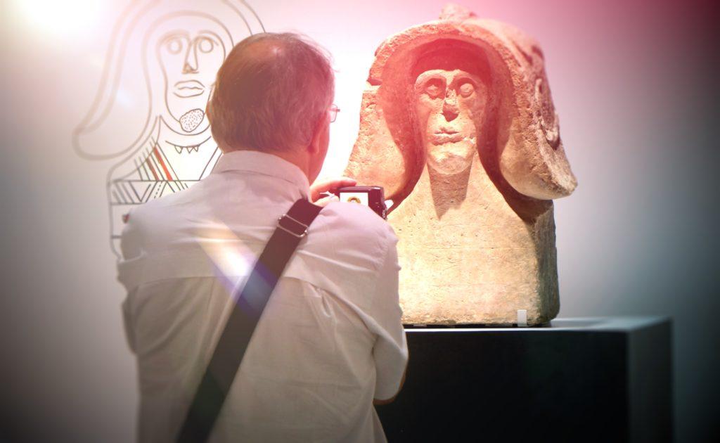 visiteur en train de photographier le buste du Guerrier de Sainte Anastasie