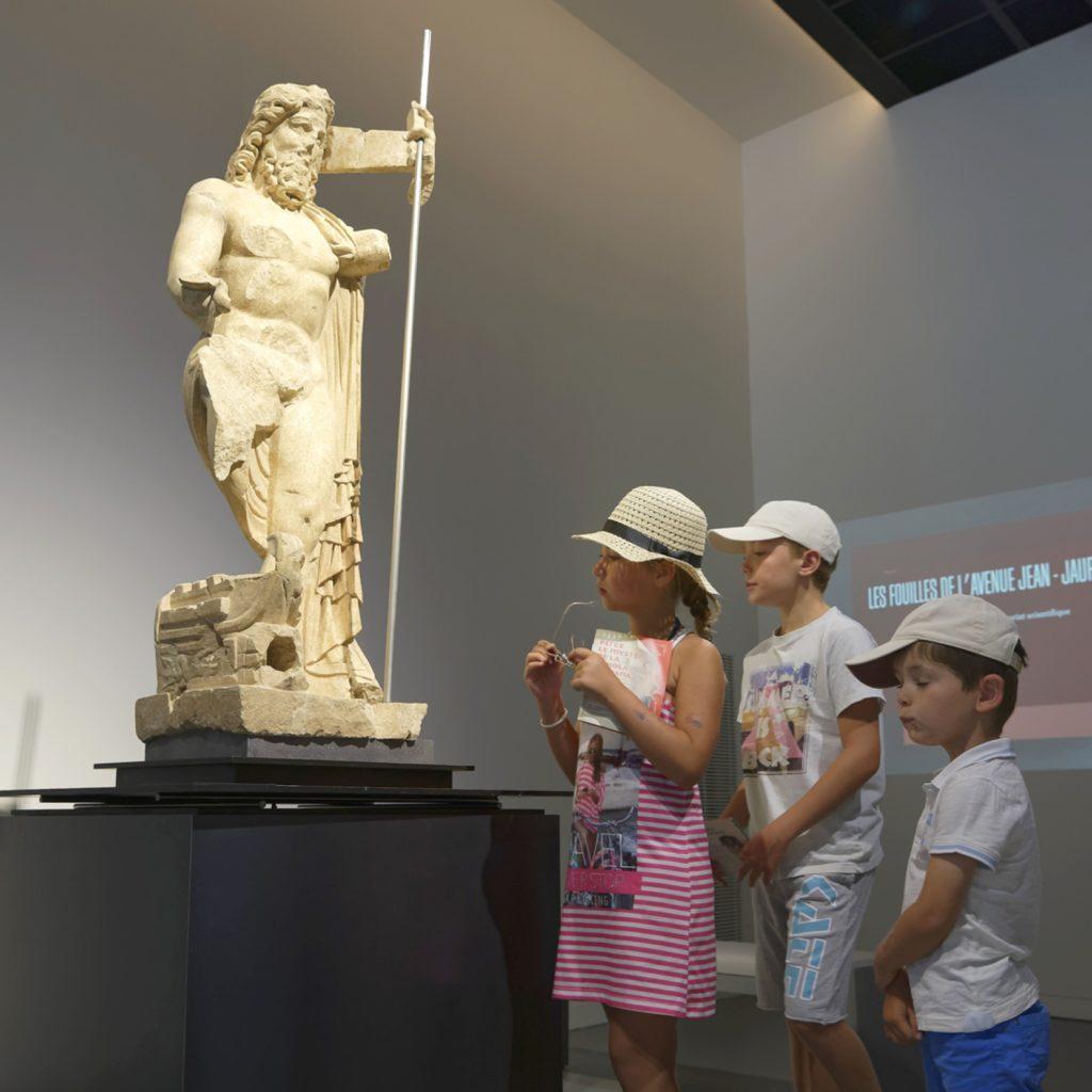 trois enfants regardent une statue représentant Neptune