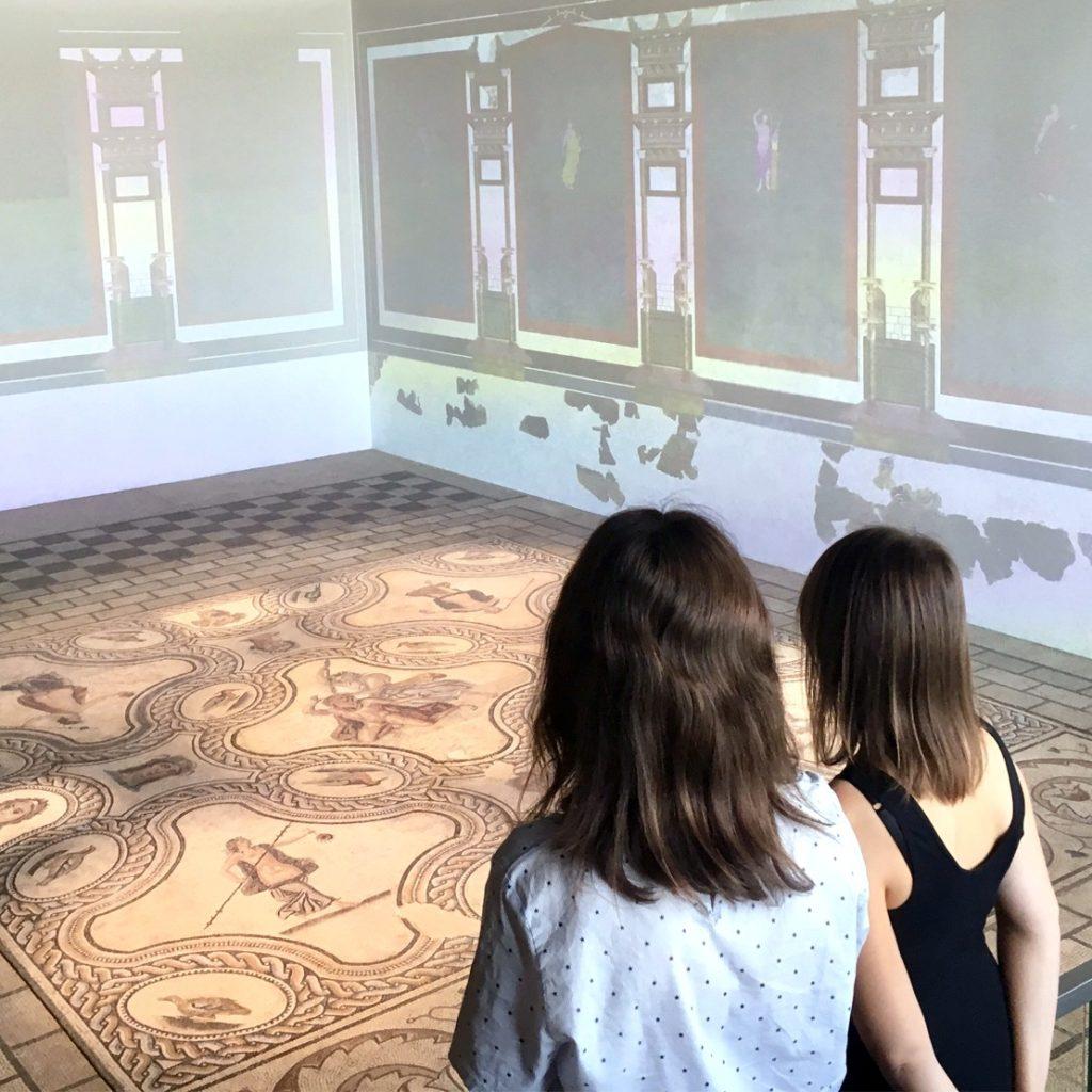 deux jeunes femmes contemplant la mosaïque de Penthée