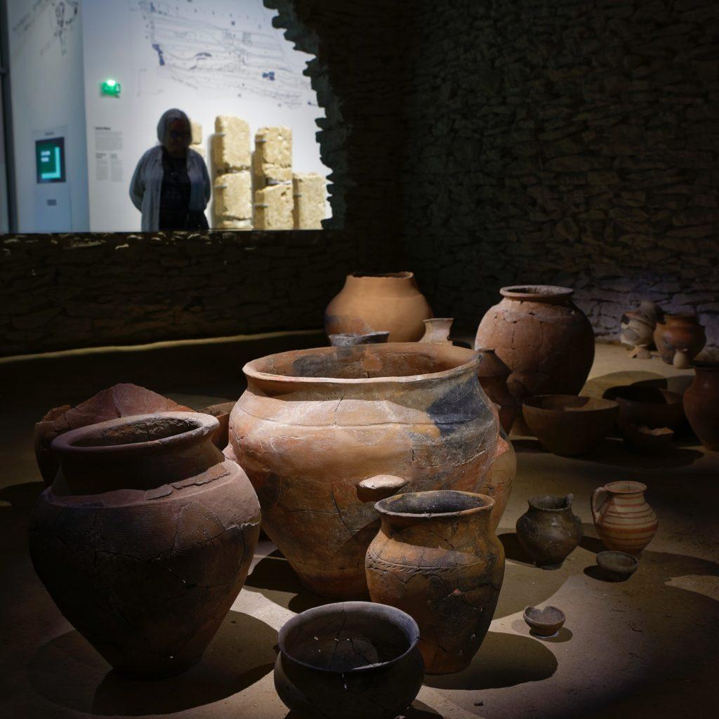 femme observant la reconstitution de l'intérieur de la maison de Gailhan et ses céramiques
