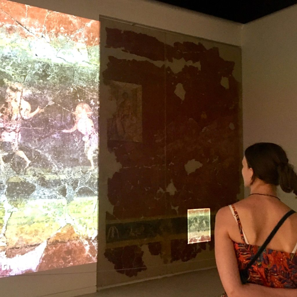 jeune femme observant les vestiges du décor de la domus Villa Roma