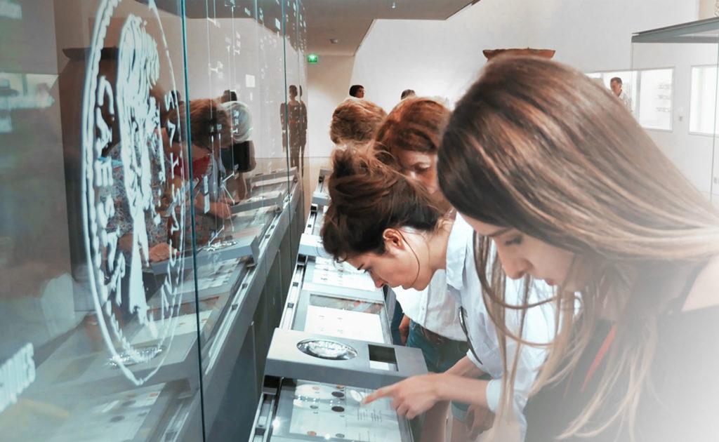 visiteurs observant pièces antiques à la loupe
