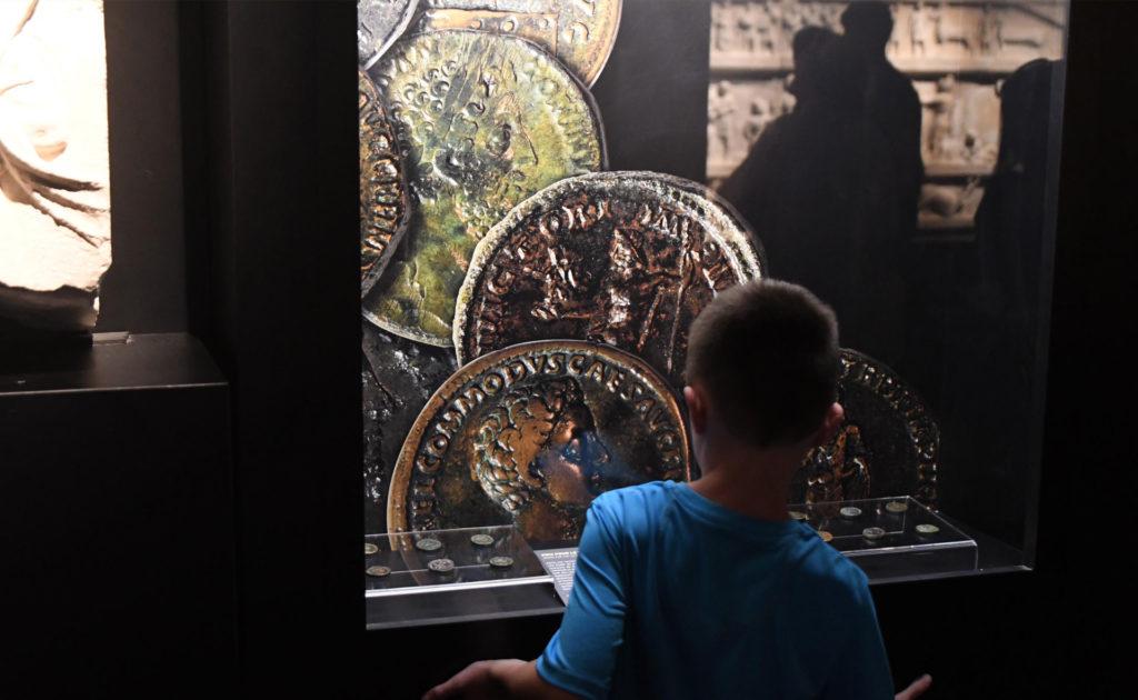 jeune garçon devant une vitrine de l'exposition sur les gladiateurs
