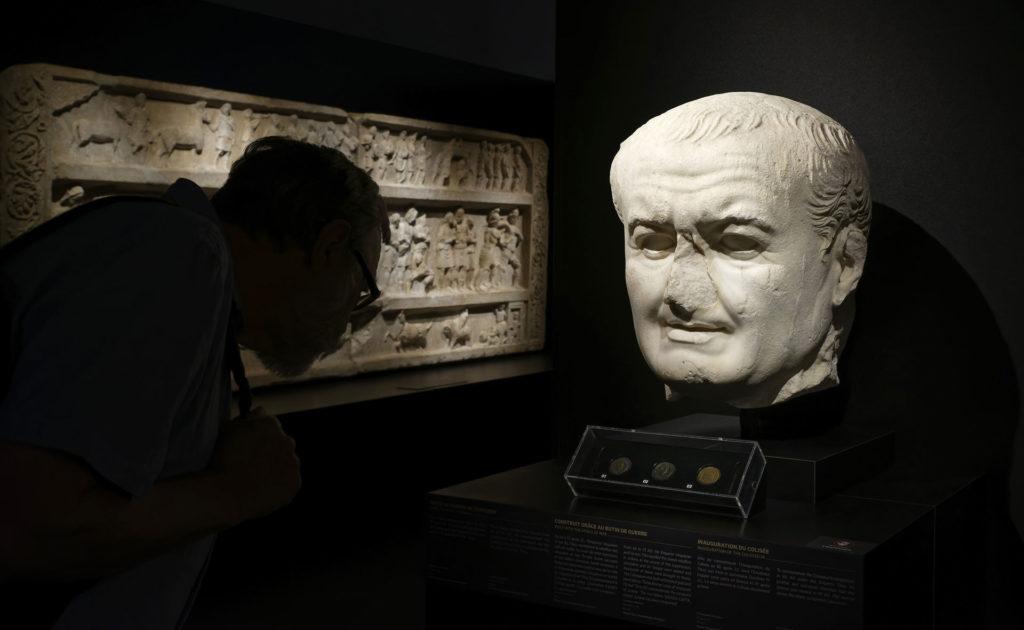 visiteur devant une tête de statue dans l'exposition sur les gladiateurs
