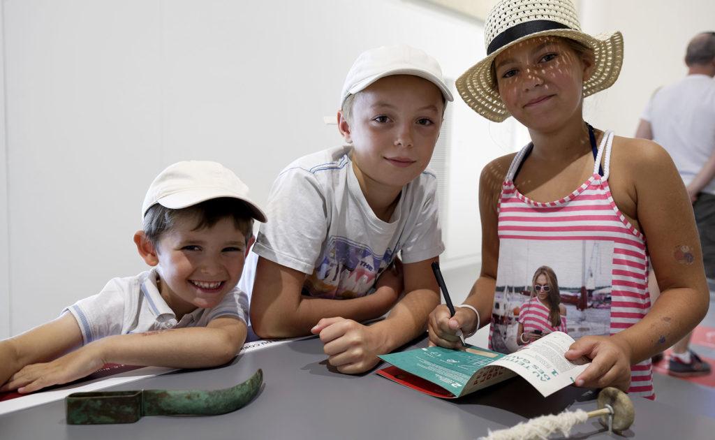 3 enfants remplissant le carnet de la Schola Romana